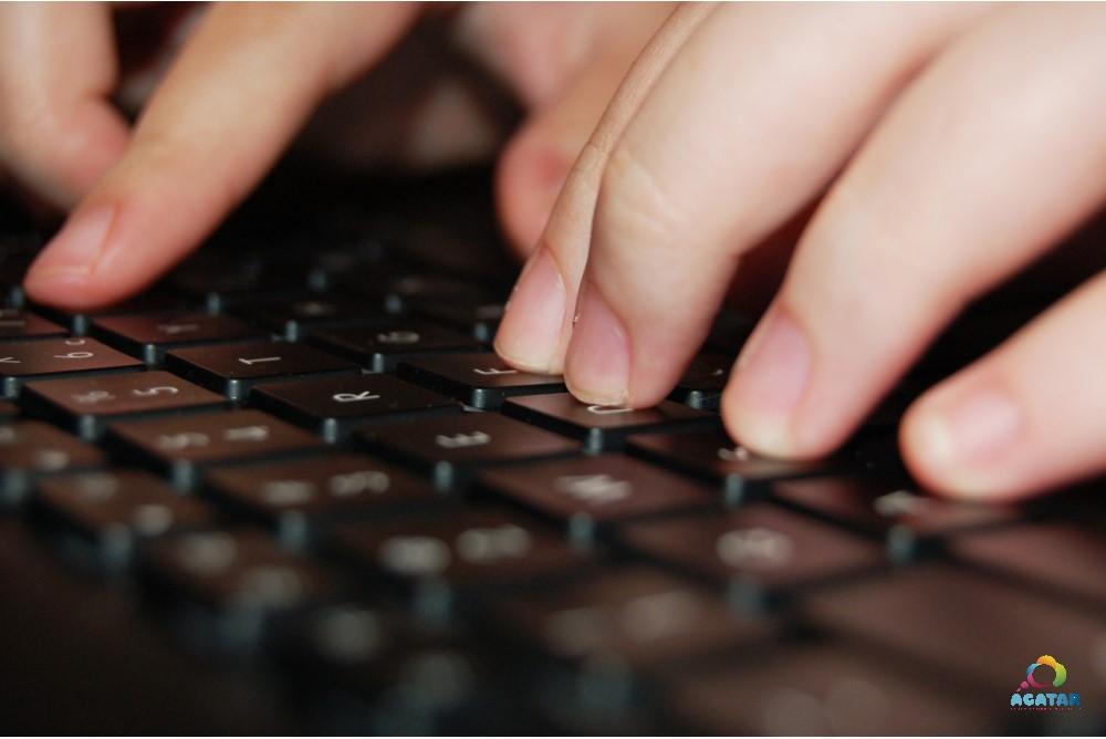 Una persona teclea en un ordenador.